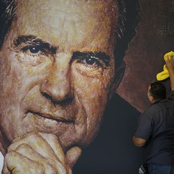 In this Wednesday, Oct. 5, 2016 photo, Tayron Santos cleans the newly-installed wall mural of former President Richard Nixon in the lobby area of the Richard Nixon Presidential Library and Museum in Yorba Linda, Calif. The museum reopened Friday, Oct. 14, 2016, following a $15 million makeover aimed at bringing the country's 37th president closer to younger generations less familiar with his groundbreaking trip to China or the Watergate scandal.