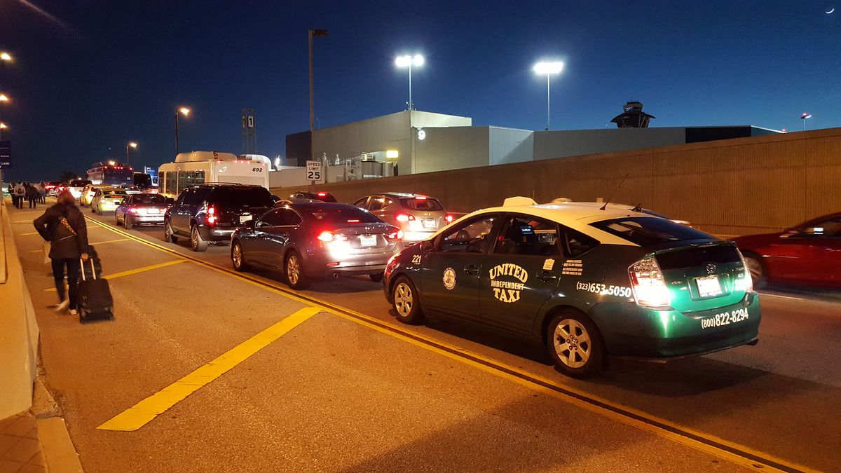 Cars at a standstill with passengers walking alongside