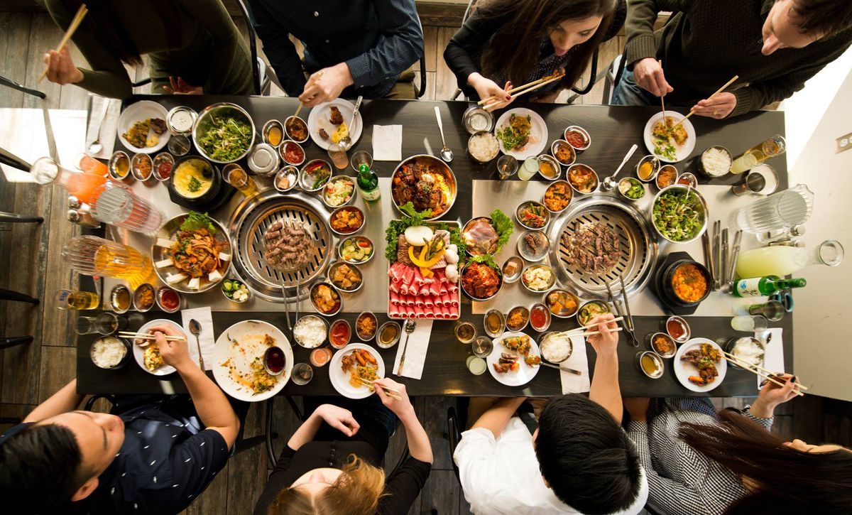 Customers sit at a table surrounded by a huge spread of Korean barbecue.