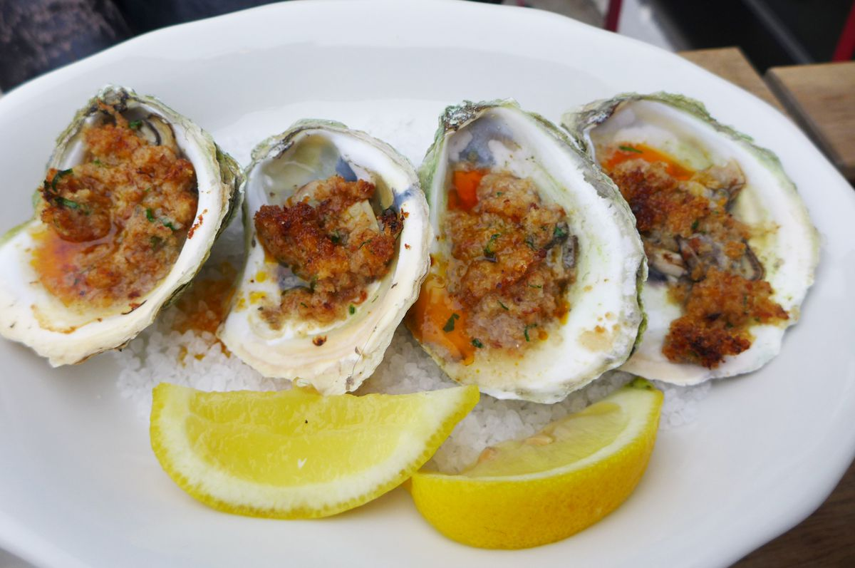 Four oysters with stuffing, a couple of lemon wedges in the foreground.