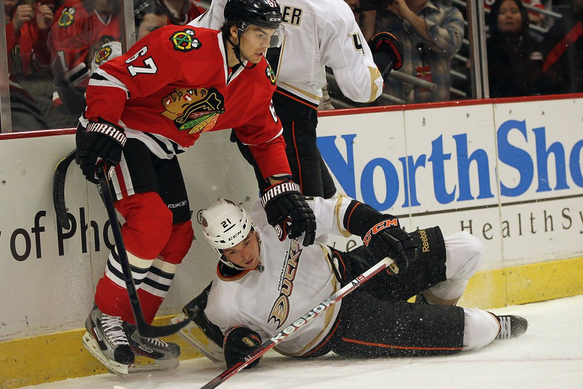 CHICAGO, IL - DECEMBER 16: Sheldon Brookbank #21 of the Anaheim Ducks slips and falls next to Michael Frolik #67 of the Chicago Blackhawks at the United Center on December 16, 2011 in Chicago, Illinois. (Photo by Jonathan Daniel/Getty Images)