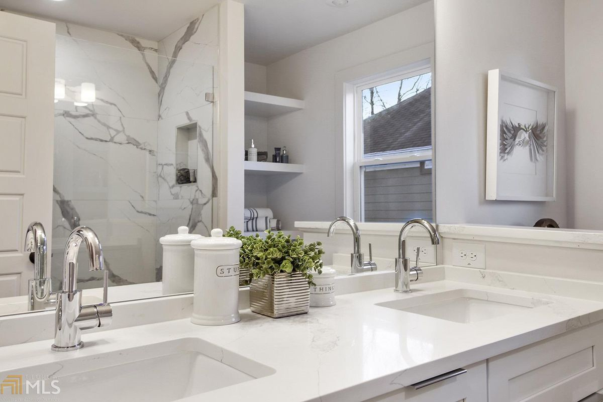 Bathroom with double vanity, shower and built-in shelves.