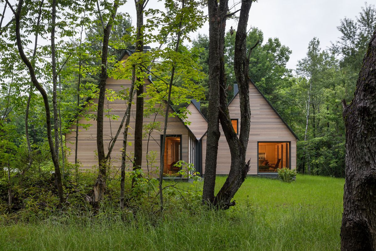 Three simple high-pitch roof structures clad in natural wood sit on a forest site surrounded by trees.