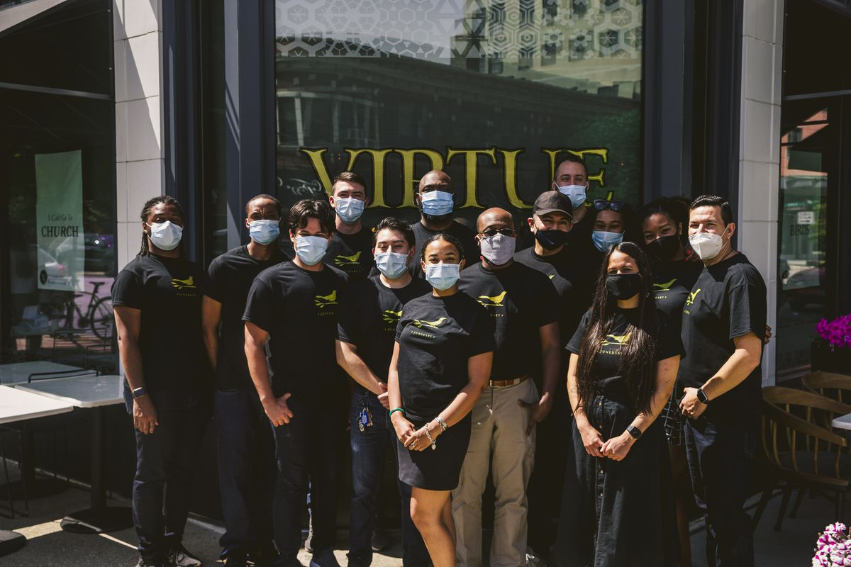 A group of restaurant workers outside a restaurant.