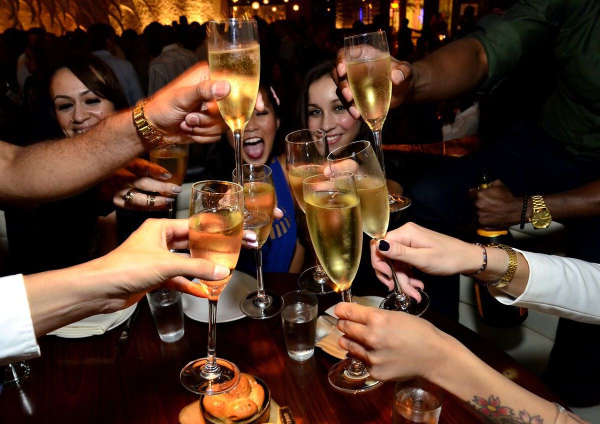 A group of men and women toasting with filled champagne flutes.