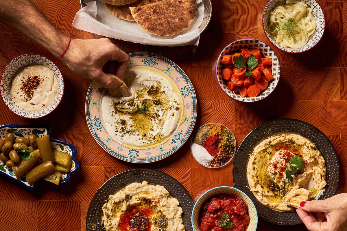An overhead shot of a lot of Israeli food plates as hands dip in.