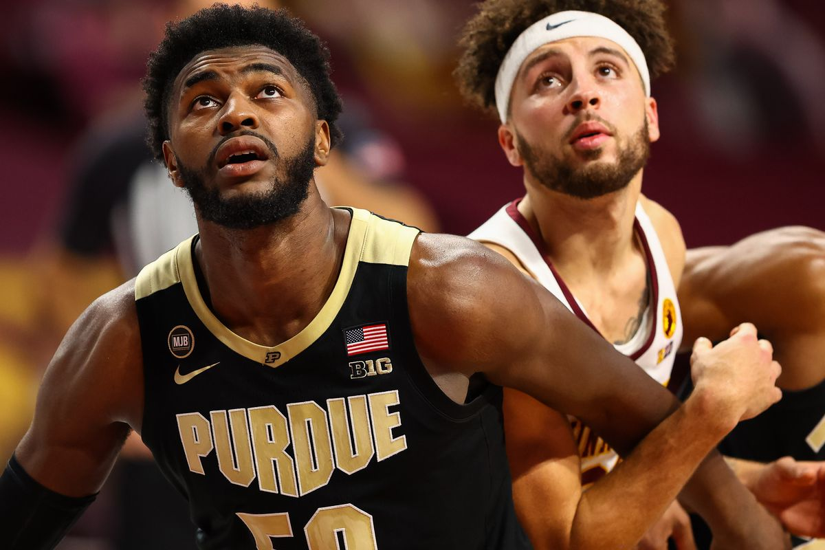 Purdue Boilermakers forward Trevion Williams and Minnesota Gophers guard Gabe Kalscheur attempt to rebound the ball during the second half at Williams Arena.
