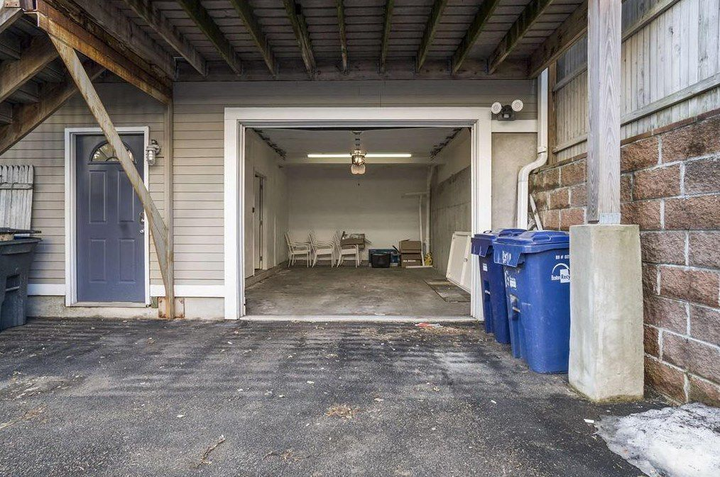 An open and empty garage beneath a deck and next to some waste bins.