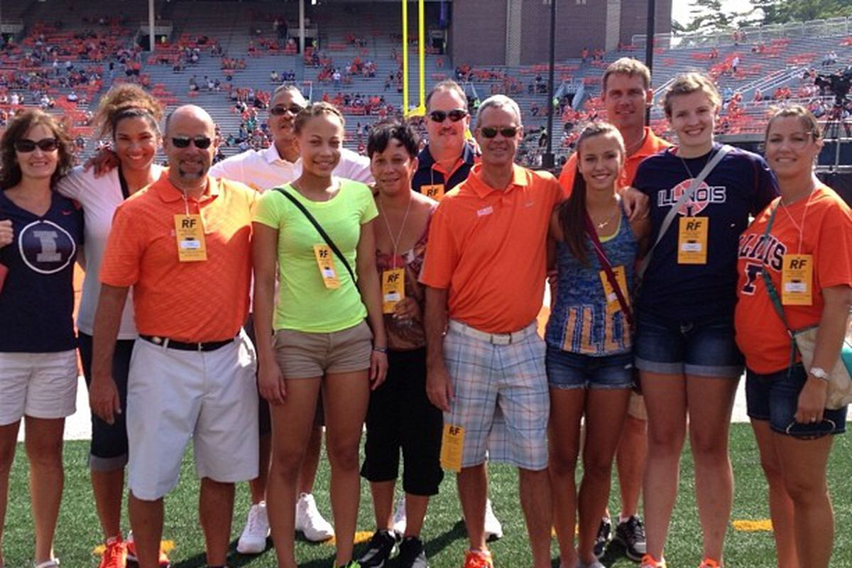 Cayla McMorris with the coaches, parents, Brooke Kissinger and Shatrice White (UI commits) on the field at a football game during her visit.