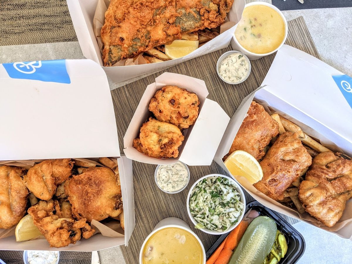 Overhead view of white takeout boxes and cups full of fried seafood and fries with lemon wedges, pickles, slaw, and chowder, spread across a light wooden table.