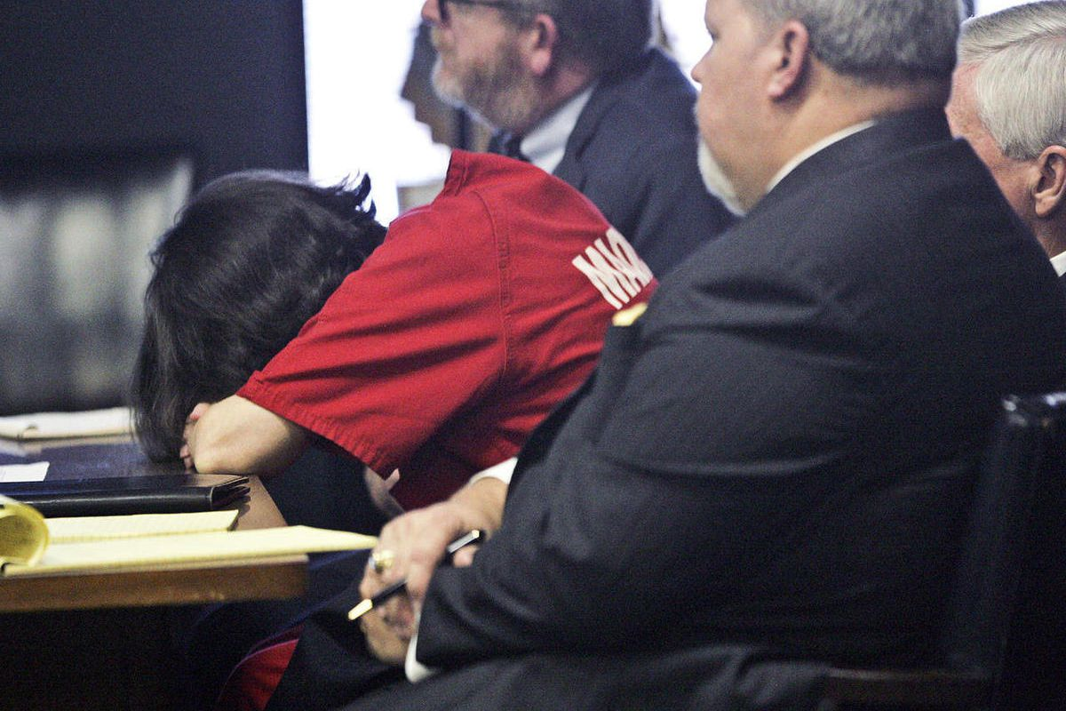 Dr. Amy Bishop puts her head down on the table as crime scene photographs from the shooting at the Shelby Center are shown to the jury, Monday, Sept. 24, 2012 at Madison County Courthouse in Huntsville, Ala. Bishop was sentenced to life without parole for