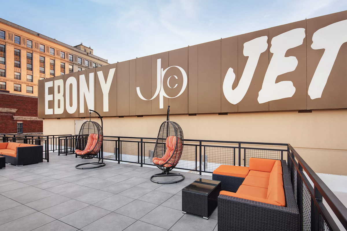 """A patio with outdoor lounge furniture under a large sign reading """"Ebony and Jet."""""""