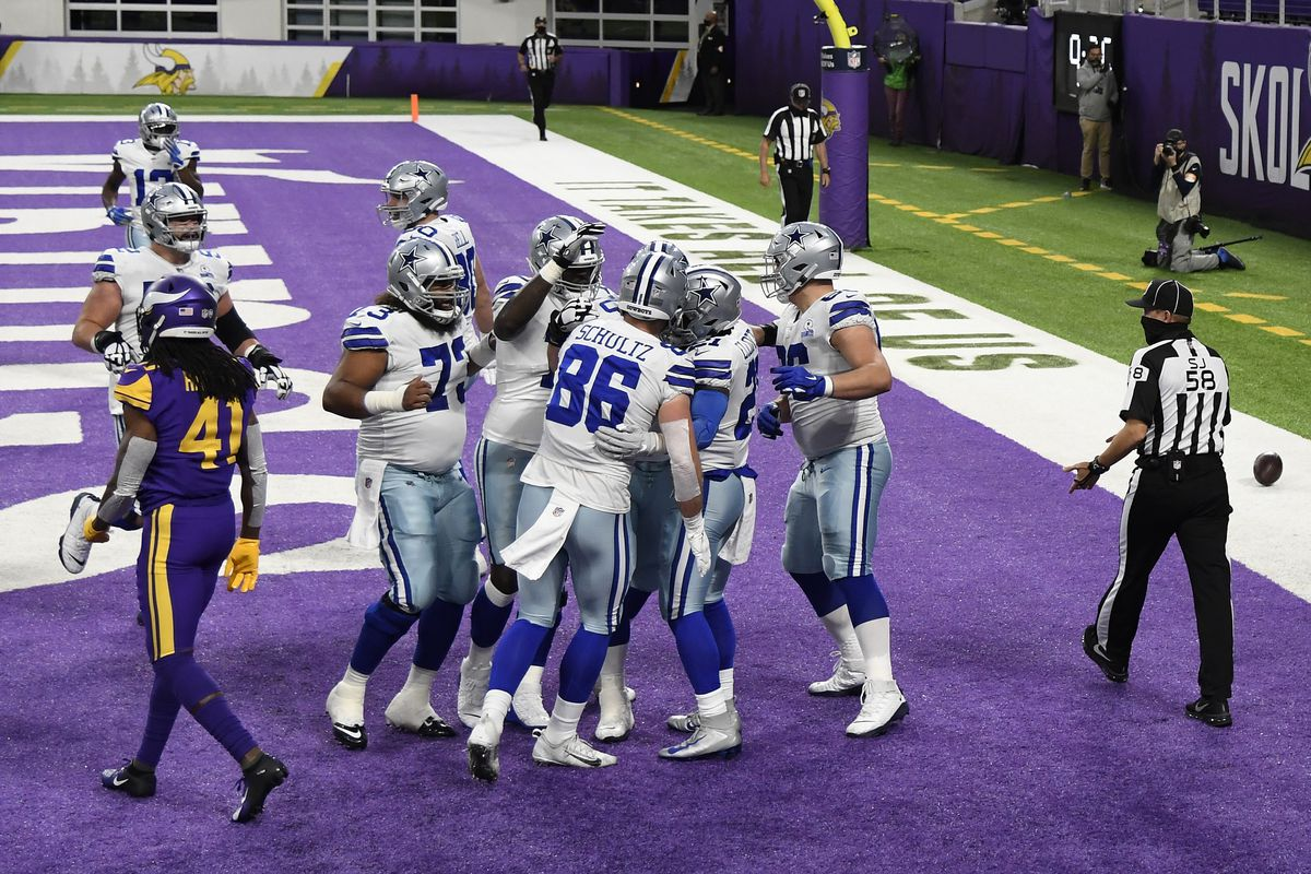 Ezekiel Elliott #21 of the Dallas Cowboys celebrates with his team after running for a touchdown against Eric Kendricks #54 and Anthony Harris #41 of the Minnesota Vikings during their game at U.S. Bank Stadium on November 22, 2020 in Minneapolis, Minnesota.