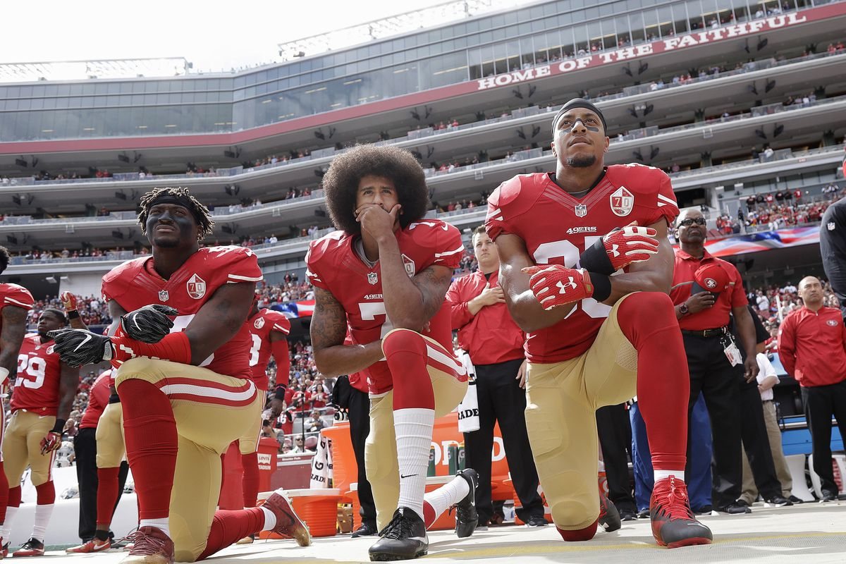 In this Oct. 2, 2016, file photo, from left, San Francisco 49ers outside linebacker Eli Harold, quarterback Colin Kaepernick and safety Eric Reid kneel during the national anthem.