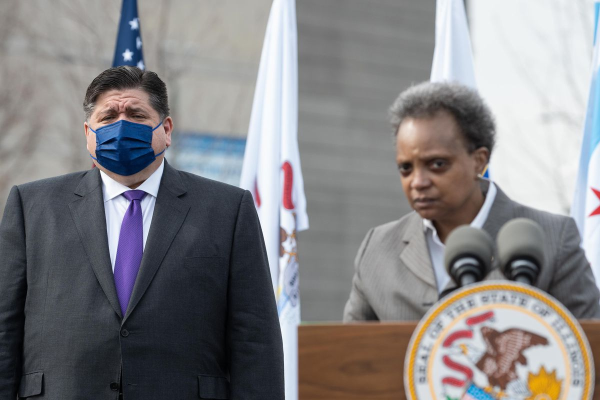 Mayor Lori Lightfoot speaks as Gov. J.B. Pritzker listens during a news conference outside the United Center in March.