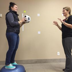 Concussion therapist Lauren Ziaks, right, and aide Allie Lee work on balance exercises that help reprogram the brain.
