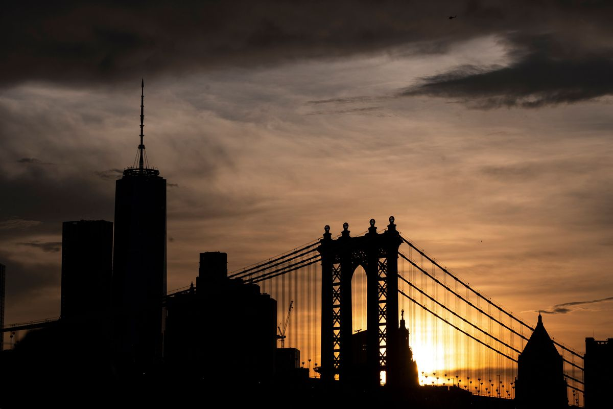 The sun sets behind the skyline of midtown Manhattan and the Manhattan Bridge on July 21, 2019 in New York City.