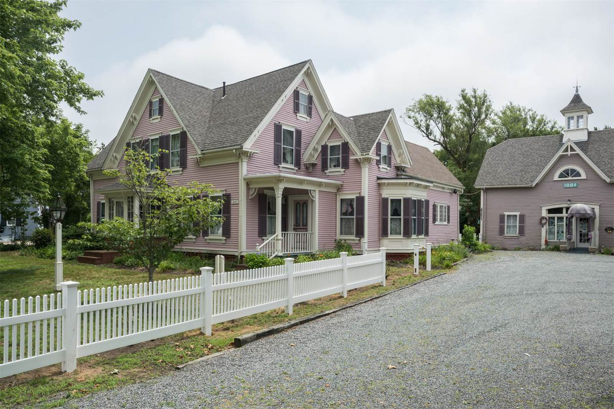 A pink, wooden Victorian home with white trime and purple shutters sits behind a white picket fence. A small carriage house sits beside it.