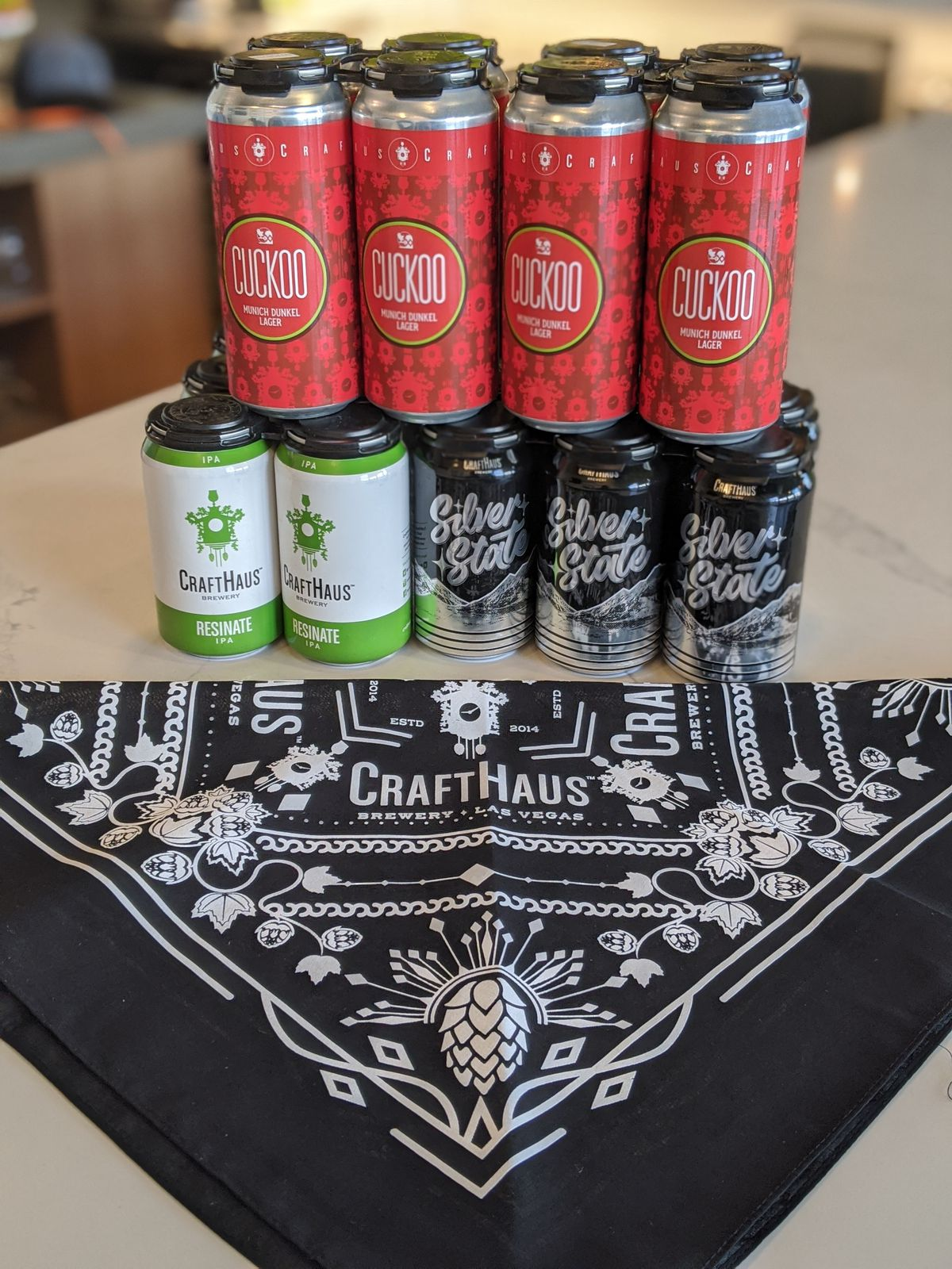 A black and white bandana with cans of beers behind it