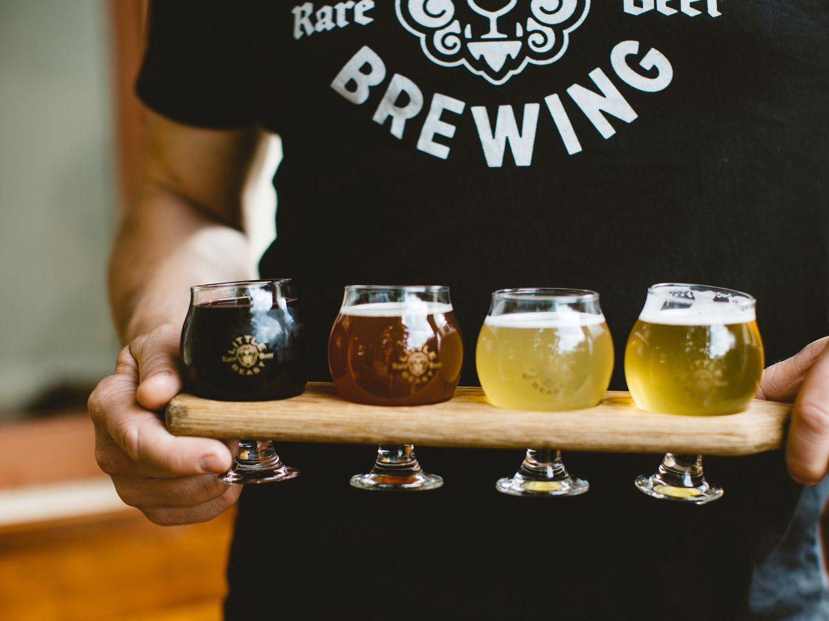 A man in a Little Beast shirt holds a tasting tray with four small glasses of beer, ranging from pale yellow to black.