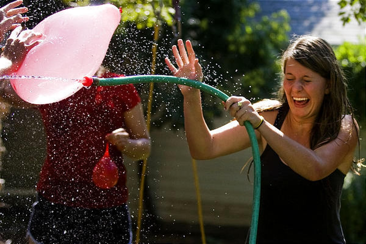 Morgan Mabey, 16, of Salt Lake City, attempts to block a massive water balloon in her backyard during a water fight on Friday. Mabey and seven of her friends got a chance to cool off as they celebrated the 17th birthday of Mark Bell, of Salt Lake City, wi