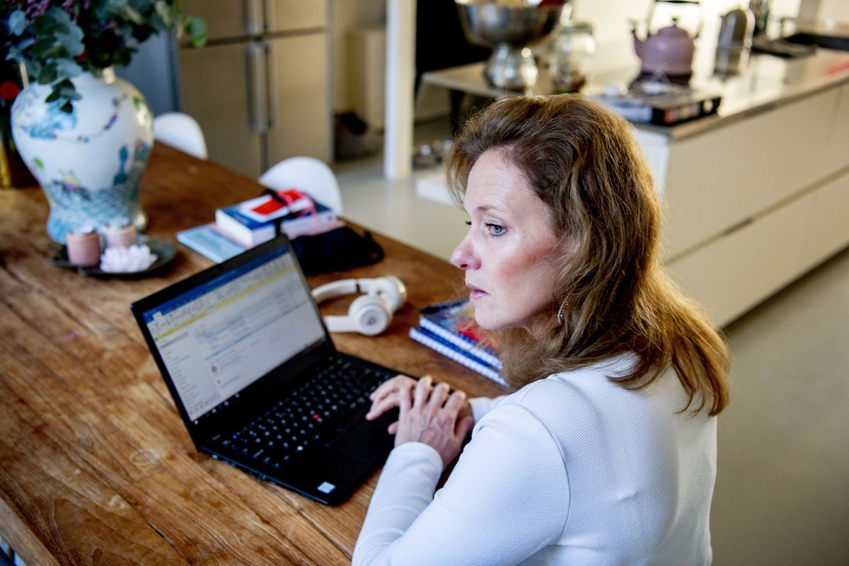 A woman seated in front of a laptop in her home office looks to the side.