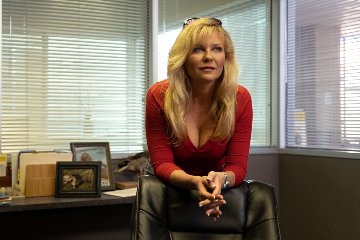"Actress Kirsten Dunst as Krystal Stubbs standing in an office leaning on a desk chair in the Showtime series ""On Becoming a God in Central Florida."""