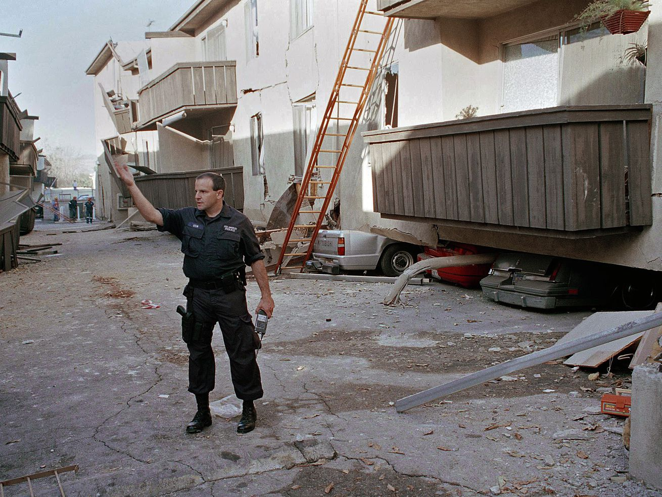 In this Jan. 17, 1994 file photo, a Los Angeles police officer stands in front of the Northridge Meadows Apartment building, after the upper floors of the structure collapsed onto the open garages and first story, killing 16 people.