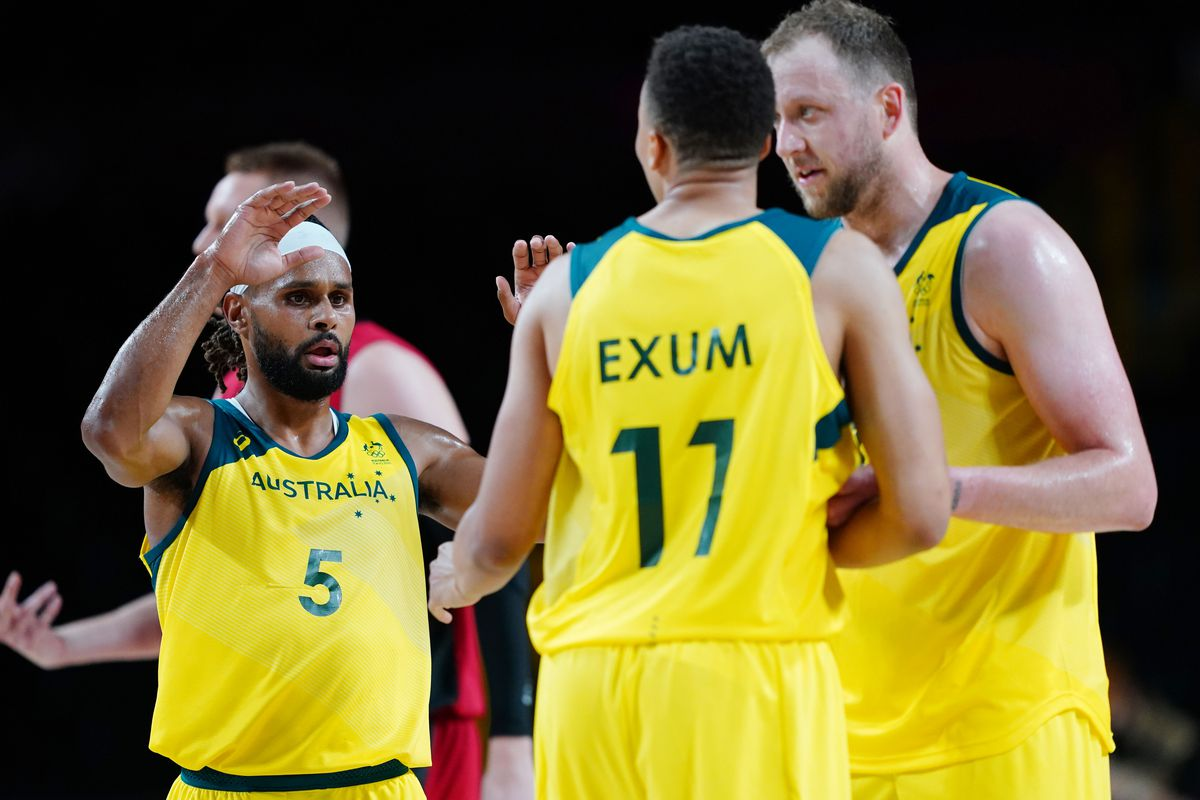 Australia player Patty Mills (5), left, is congratulated by his teammates after hitting a three point shot during the Tokyo 2020 Olympic Summer Games at Saitama Super Arena.