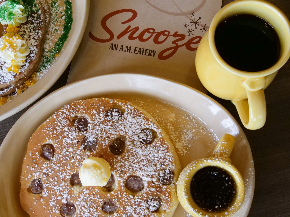 A close-up of a plate of pancakes with butter and syrup next to a cup of coffee at Snooze