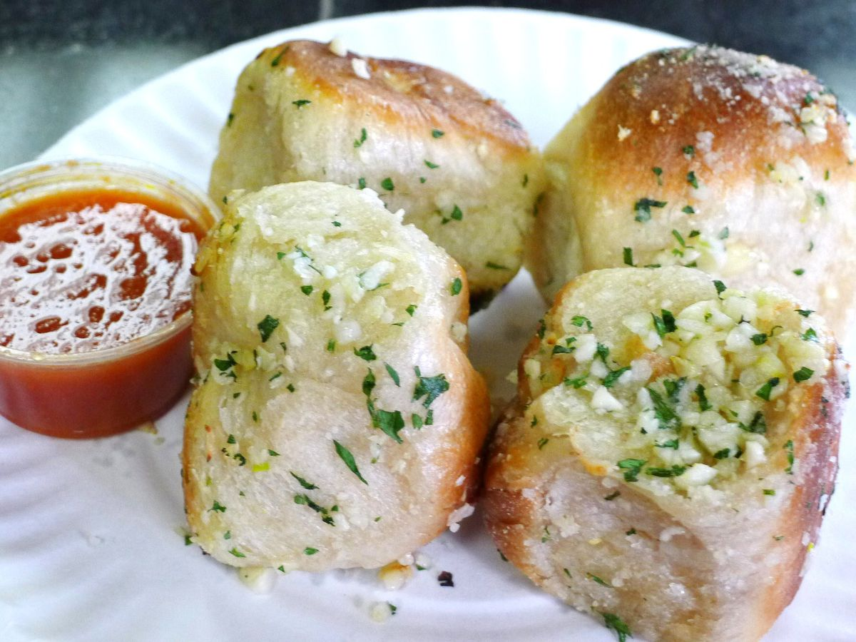 Buns dotted with chopped garlic and parsley, with tomato sauce on the side