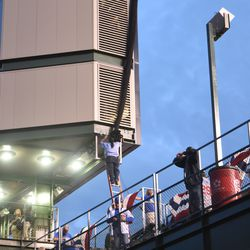 6:10 p.m. The protective netting for the left field video board being secured -
