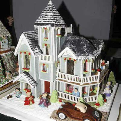 Gingerbread house in the shape of Queen Anne style home, with marzipan people placed around it.