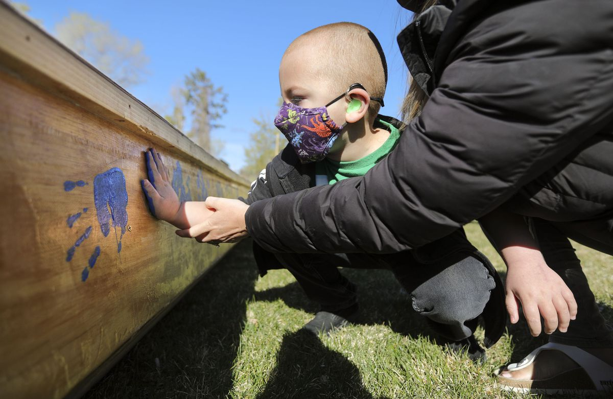 Kahnrad Koontz, a pre-k student at the Utah Schools for the Deaf and the Blind, puts his handprint on All Hands on Deck.