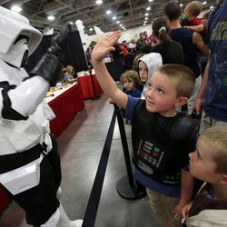 A Stormtrooper gives a high five to Harper Brace, dressed as Darth Vader, at Comic Con at the Salt Palace Convention Center in Salt Lake City on Saturday, Sept. 7, 2013.