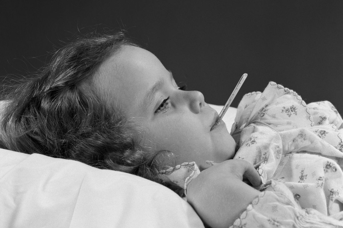 A black and white photo of a young girl with a thermometer in her mouth.