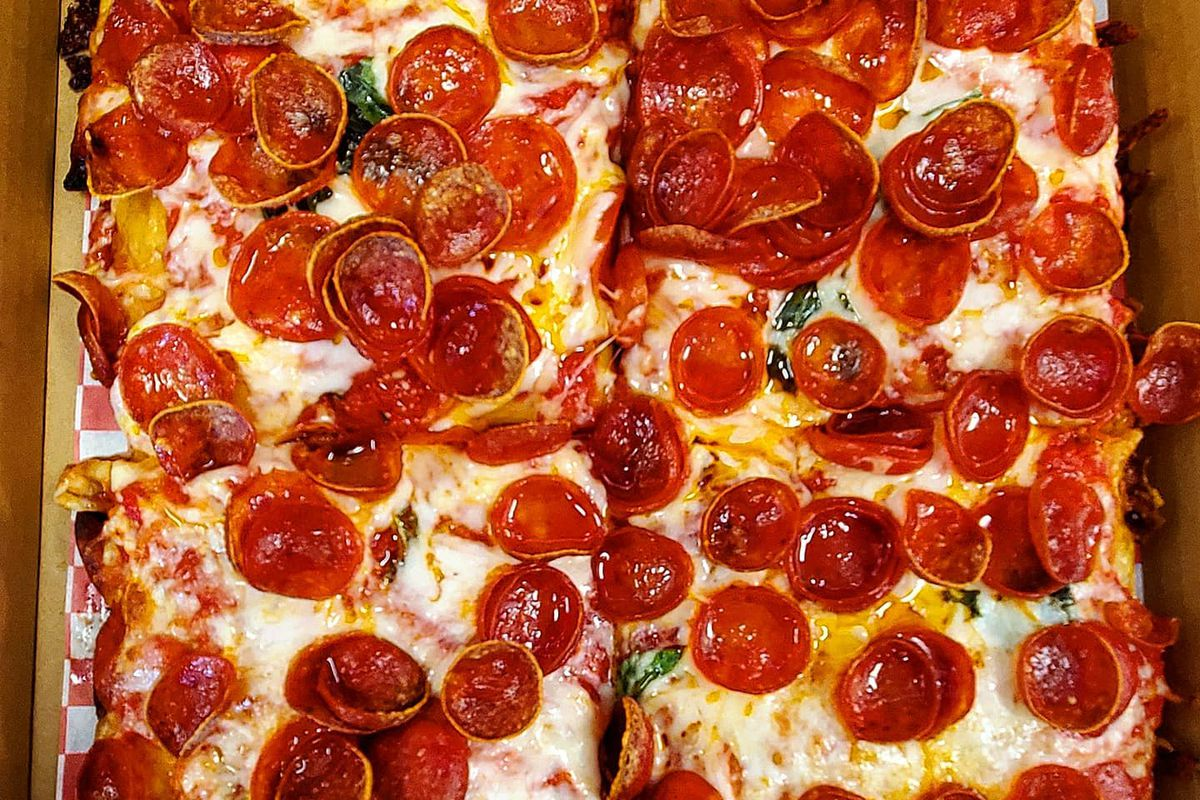 Four square slices of pepperoni pizza