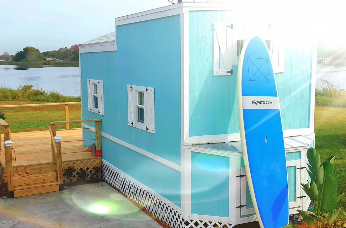The exterior of a tiny house in Florida. The facade is blue with white decorative details. There is a wooden deck. The house is near a body of water.