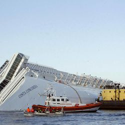 FILE - In this Tuesday, Jan. 24, 2012 file photo, a sea platform carrying a crane approaches the grounded cruise ship Costa Concordia off the Tuscan island of Giglio, Italy. Costa Crociere SpA says work to remove the capsized Costa Concordia cruise ship from its rocky perch off Tuscany will begin early next month and is expected to take 12 months. Costa said in a statement Saturday, April 21, 2012, the U.S.-owned company Titan Salvage won the bid to remove the ship, which struck rocks off the tourist-dependent island of Giglio on Jan. 13, when the captain made an unauthorized maneuver too close to shore.