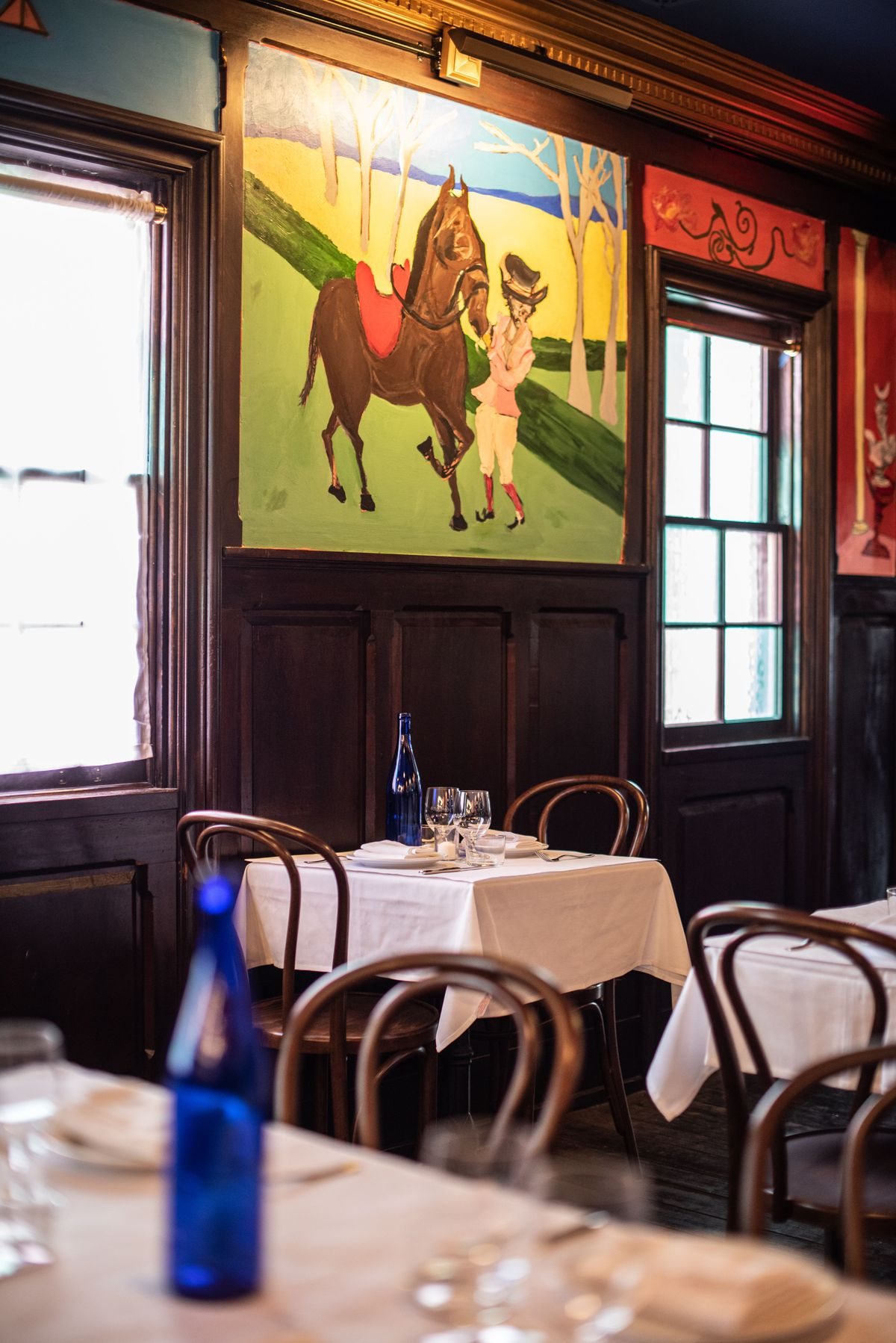 A lit, green painting of a horse inside of an aging restaurant dining room.