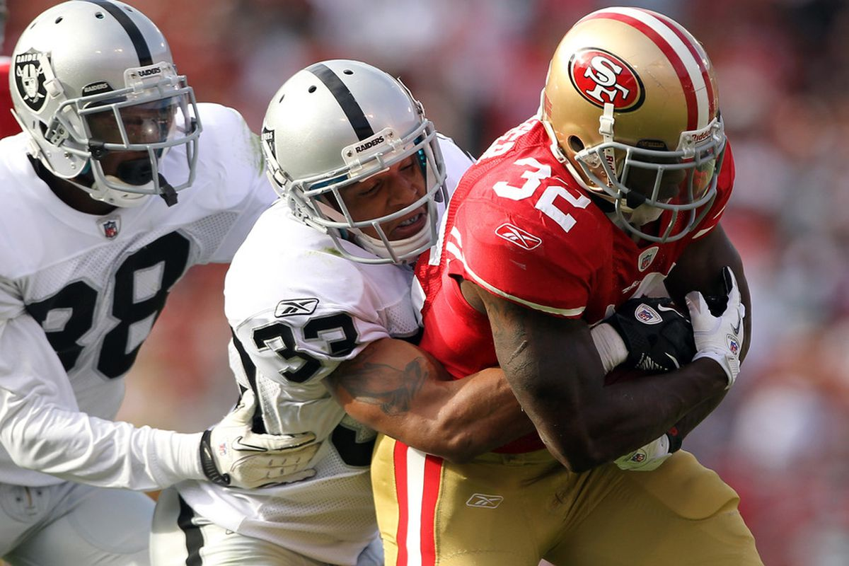 SAN FRANCISCO, CA - AUGUST 20:  Kendall Hunter #32 of the San Francisco 49ers is tackled by Tyvon Branch #33 of the Oakland Raiders at Candlestick Park on August 20, 2011 in San Francisco, California.  (Photo by Ezra Shaw/Getty Images)