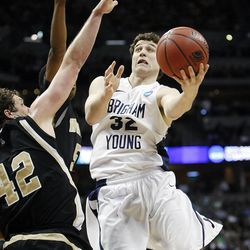 BYU's Jimmer Fredette shoots around Wofford's Noah Dahlman on Thursday, March 17, 2011, in the second round of the NCAA Tournament in Denver. Fredette, now with the Sacramento Kings, is suing Utah-based clothing company Black Clover Enterprises for allegedly failing to pay him and using his name and likeness for profit.