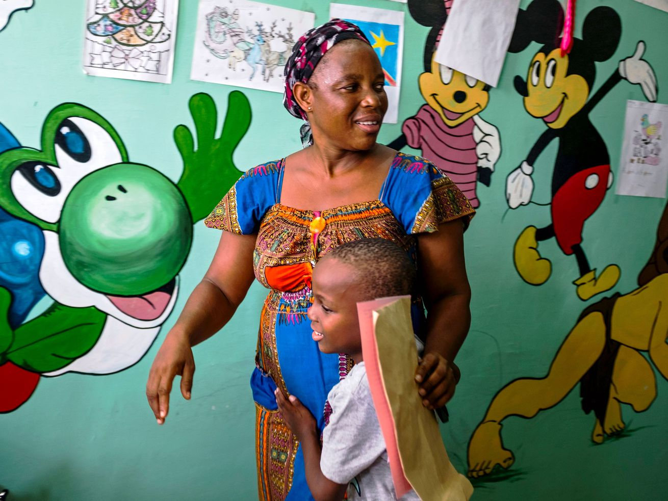 A mother embraces her son, who suffers from malaria, in a pediatric clinic featuring a wall mural of cartoon character.