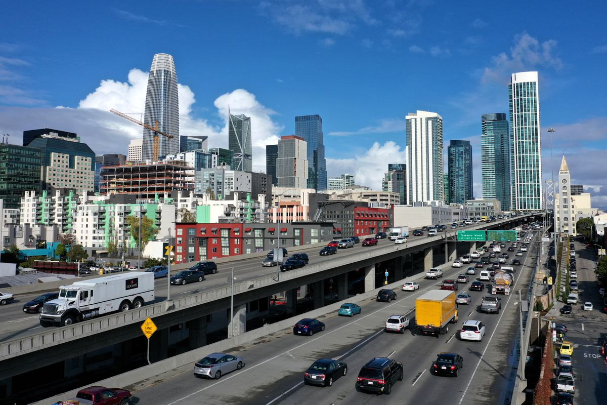 Traffic on a busy freeway, photographed from above, with tall, glass-encased high-rises visible on the horizon.