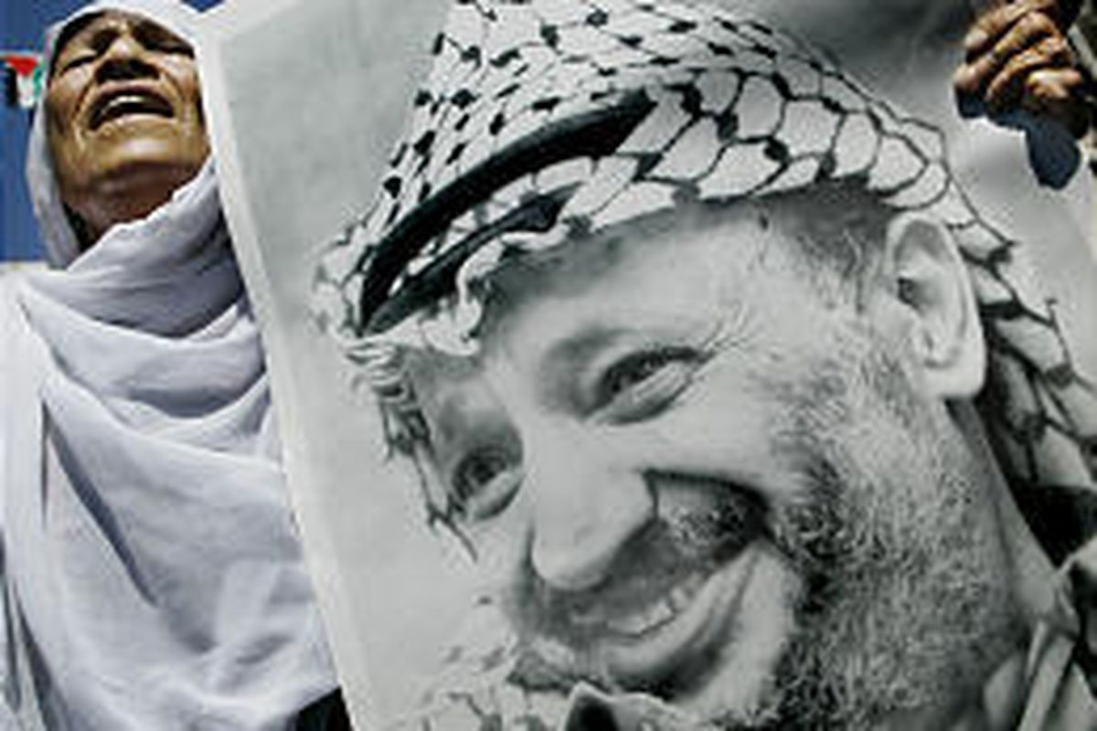 """A woman carries a picture of Yasser Arafat during a rally supporting the Palestinian in Gaza City Monday. The Israeli decision to """"remove"""" Arafat has boosted his popularity."""