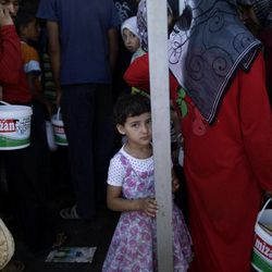 A Syrian girl, bottom center, who fled her home, due to fighting between the Syrian army and the rebels, waits her turn to buy bread and eggs from a store, as she and others take refuge at the Bab Al-Salameh border crossing, in hopes of entering one of the refugee camps in Turkey, near the Syrian town of Azaz, Monday, Sept. 3, 2012.