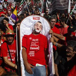 A man performs representing Spanish Prime Minister's Mariano Rajoy dead as a protest against austerity measures applied by the Spanish government, in  Columbus Square in Madrid, Spain, Saturday, Sept. 15, 2012. Tens of thousands of people from all over the country converged on Madrid to hold a large anti-austerity demonstration on Saturday. By mid-morning several major roads had been blocked as buses unloaded protesters at 10 rendezvous points from which marches began. The demonstration was called to protest government cuts during the country's financial crisis.