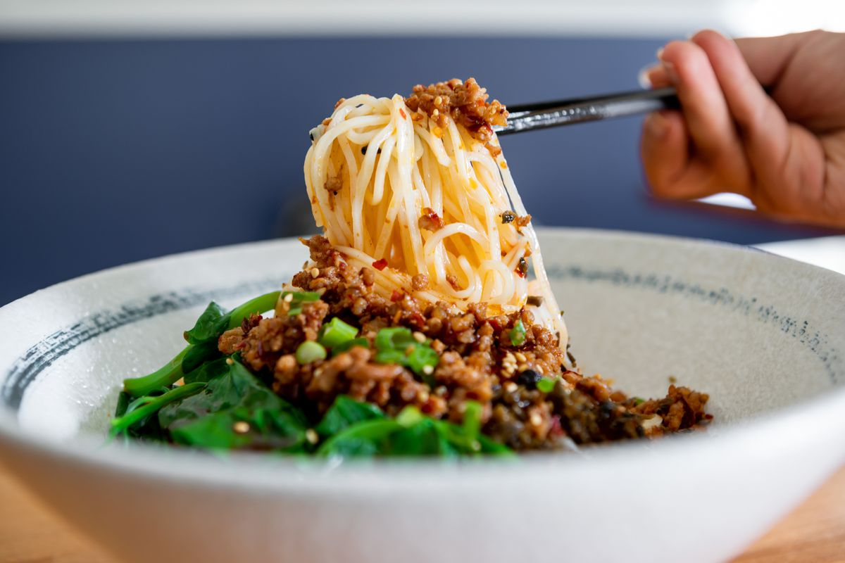 A diner picks up a portion of Sichuan-style noodles topped with meat sauce and fresh Chinese greens