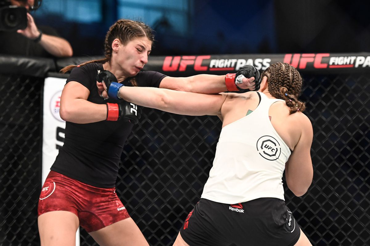 Liana Jojua (red gloves) fights Sarah Moras (blue gloves) during UFC 242 at The Arena.