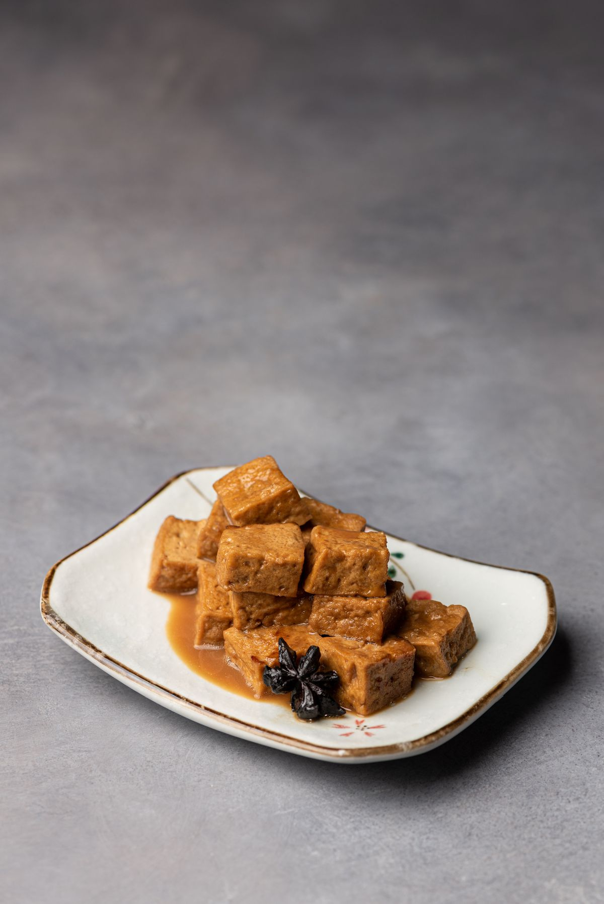 Cubes of brown braised tofu on a plate.